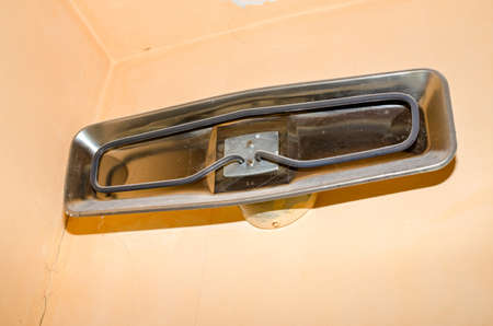 Old dusty metal heater on a bathroom wall