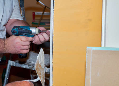 Male hands holding electric screw driver while attaching a part of a plaster board on a wall during renovation works in an apartment