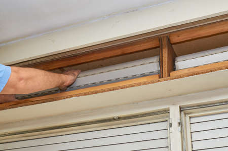 Homme fixant un vieux store dans sa boîte en bois