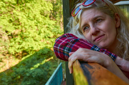 Woman dressed in a royal stewart red tartan shirt leaned out off a train window