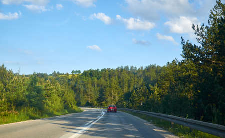 Red car on a road, driving through an idyllic countryside landscape 版權商用圖片