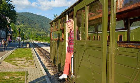 Woman dressed in a royal stewart red tartan shirt getting off a vintage train