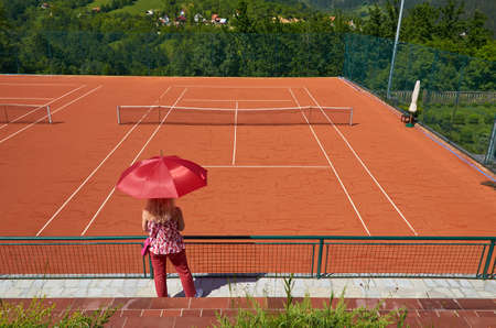 Woman with an umbrella for sun protection watching an empty tennis court on a spring day
