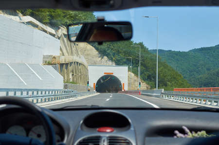 Car approaching a tunnel during a drive on a highway