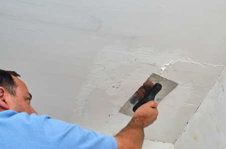 Man smoothing a ceiling with a trowel during renovating works