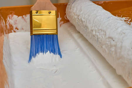 Wooden brush for painting with blue hairs in white color paint