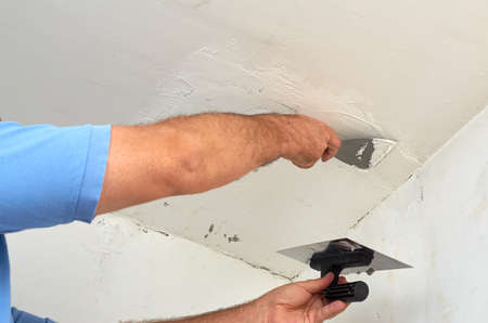 Man putting spackle on a ceiling during renovating works