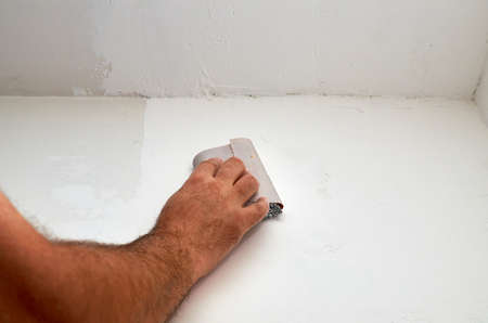 Hand holding sandpaper while polishing a wall