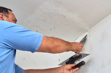 Man working with spackle during renovating works