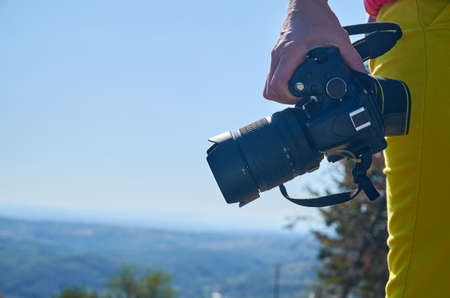 Hand holding camera and a landscape in a background Stock Photo