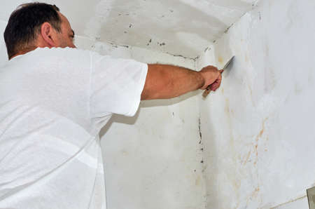 Man smoothing a wall with a spatula during renovating works