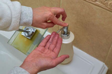 Hands while putting liquid soap from a dispenser