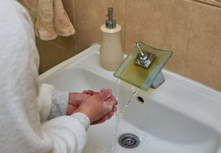 Soaping hands while washing in a bathroom Stock Photo
