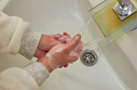 Foamy hands while washing over a sink in a bathroom