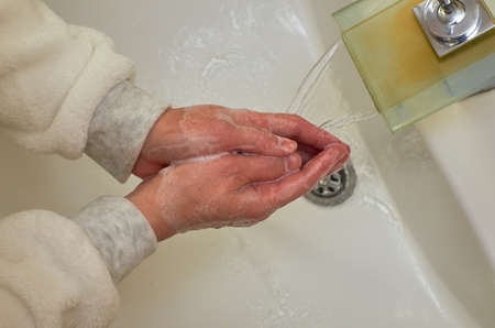 Properly washing hands over a sink while water is flowing from a faucet