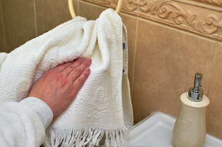 Using towel for drying hands after washing in a private bathroom. Stock Photo