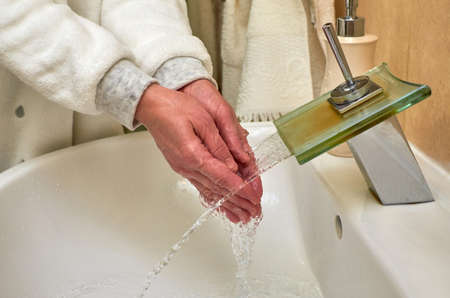 Washing hands over a sink while water is flowing from a faucet