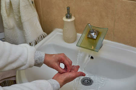 Properly washing fingers over a sink while water is flowing from a faucet