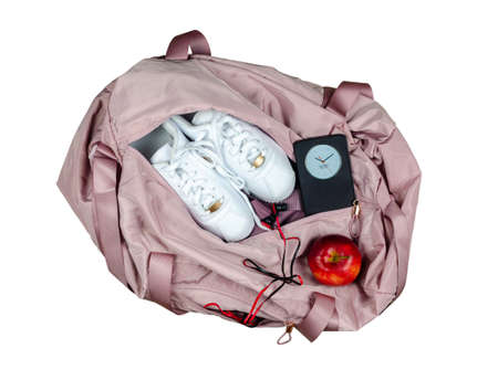 Woman's pink gym bag with white sneakers, red apple and smart phone showing time and date, isolated on white background