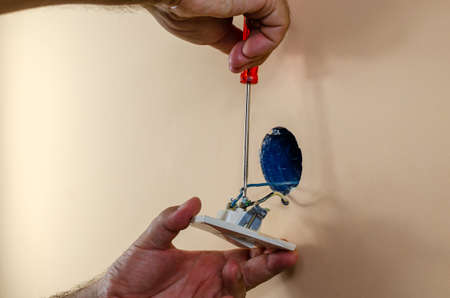 Fixing old light switch on a wall with a screwdriver Stock Photo