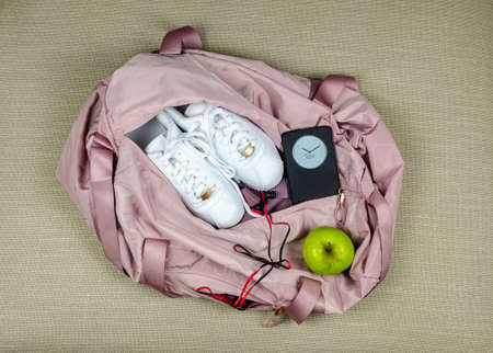 Woman's pink gym bag with white sneakers, green apple and smart phone showing time and date Stock Photo