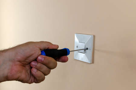Mounting or dismounting an old light switch from a wall with a screwdriver