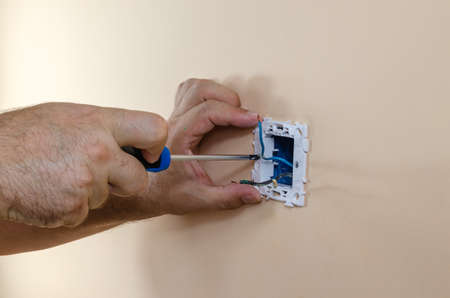 Attaching a light switch with a screwdriver to the wall