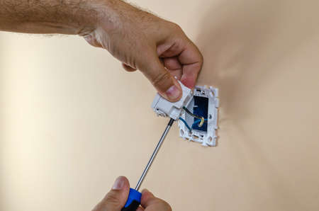 Connecting electric wires to a modular light switch on a wall with a screwdriver