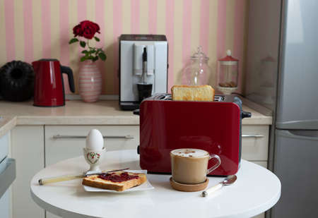 Breakfast served on a kitchen table - coffee, boiled egg and jam on bread Stockfoto