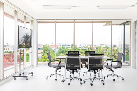 Group of conference table and chairs in white and wide office with television screen without anyone in room