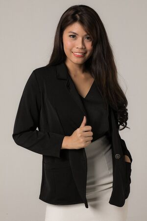 Portrait of Asian businesswoman confidently smiling in a black suit isolated from a gray background.