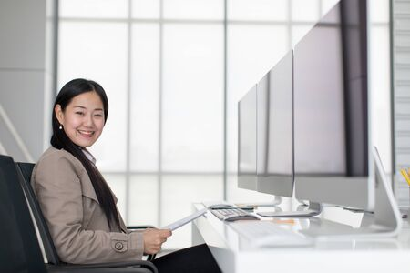 Beautiful young Asian Sitting in a modern office happily, there are many computer monitors, ideas for joyful working.