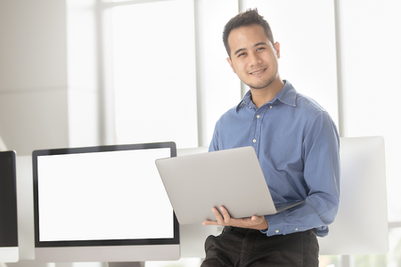 Young Asian businessman successfully smiles in a modern office with his computer. white blank screen for adding any contents