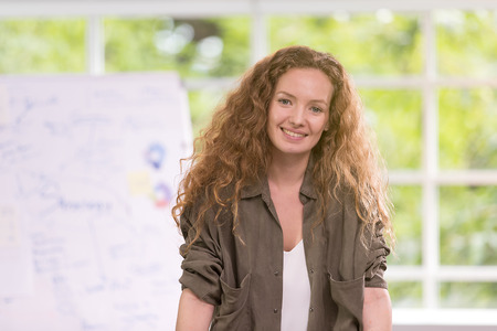 Beautiful businesswoman curly blond hair smile happily with a relaxed manner. Work successfully In the office there is a tree in the back.