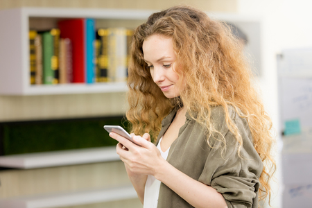 Beautiful caucasian girl with long curly blond hair is using her phone in a modern office. Stock fotó