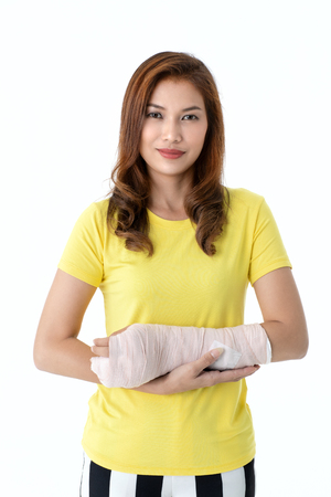Broken arm Asian woman with arm sling sponsored in her hands sitting on a wheelchair Ideas for accident Injuries and health care Studio shot on a white background. Asian woman with supported on her hand, concept for injured by accident and healthcare. Studio shot on white background.