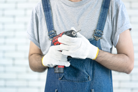 Young Asian man holding power drill standing in front of white brick wall, smiling and looking at camera, concept for home DIY Banque d'images
