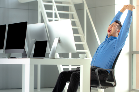 Young Asian businessman is sitting and yawn in a modern office. Banque d'images - 107036094