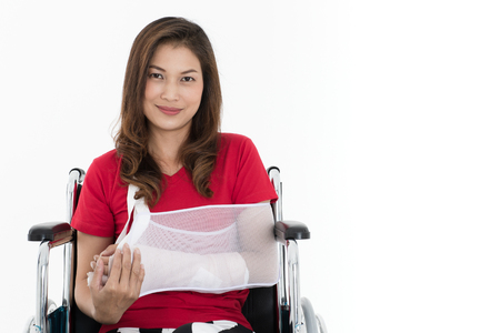 Broken arm Asian woman with arm sling sponsored in her hands sitting on a wheelchair Ideas for accident Injuries and health care Studio shot on a white background.