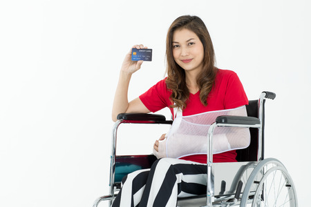 Broken Asian woman with arm sling sponsored in her hands sitting on a wheelchair Ideas for accident Injuries and health care studio photographed on a white background.