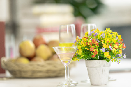 Artificial flowers beautiful colors. Placed on side table with clear glass. The back there no basket of fruit. Imagens