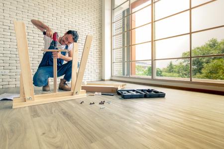 Giovane uomo che lavora come tuttofare, assemblaggio tavolo in legno con attrezzature, concetto per casa fai da te e self service. In ufficio c'è un blocco di mattoni bianchi.