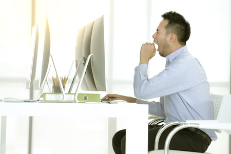 Young Asian businessman is sitting and yawn in a modern office.