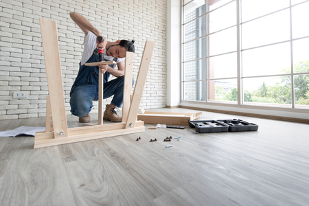 Young man working as handyman, assembling wood table with equipments, concept for home diy and self service.in the office there is a white brick block. Banque d'images