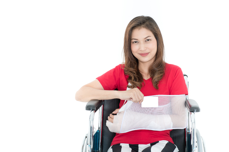 Broken arm Asian woman with arm sling sponsored in her hands sitting on wheel chair and showing blank mock up card. Ideas for accident Injuries and health care. Studio shot on a white background