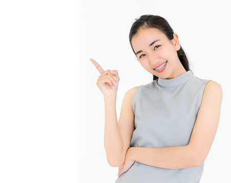 Portrait of Asian girl wearing dental braces smiling happily. Point to the separator isolated from the white background. Stock fotó - 112634001