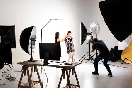 Fotografo e modello che lavora in un moderno studio di illuminazione con molti tipi di flash e accessori. Archivio Fotografico