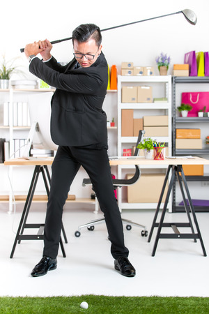 Young Asian businessman in black suit is practicing golf there is a computer placed on the desk as a background in the office.