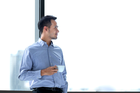 Young Asian businessman relaxed standing against window with a cup of coffee in hand and look ahead  to far point. Copy space on the right. Stock Photo