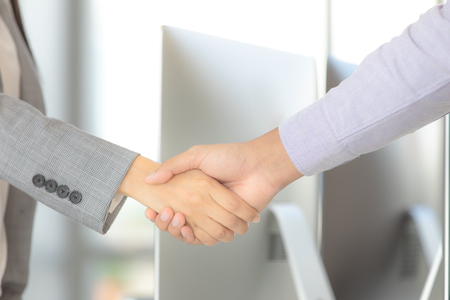 Businessman and businesswoman shake hands for work together job successful in modern office computer background.
